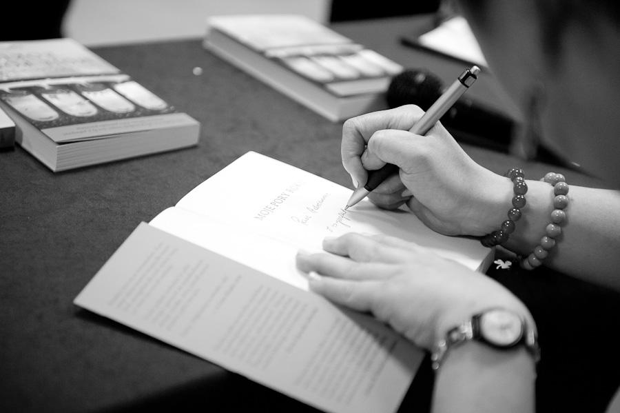 Dłonie wpisujące desykację w ksiązce